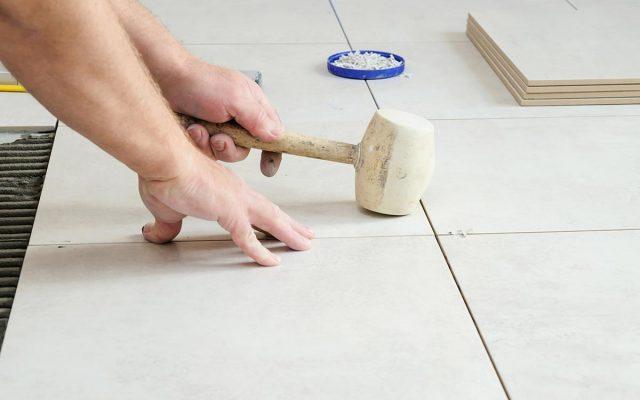 worker-s-hend-is-knocking-rubber-hammer-tile-better-gluing